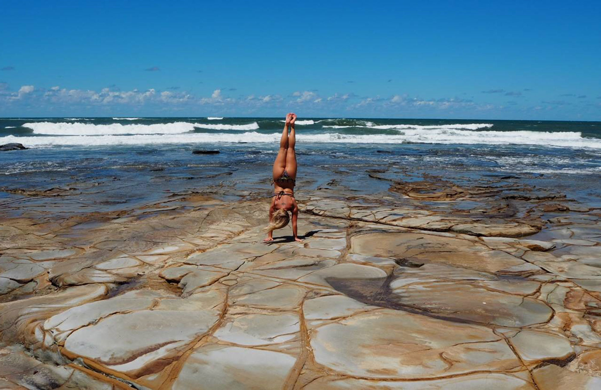 malin an exchange student in australia is doing a handstand at the beach