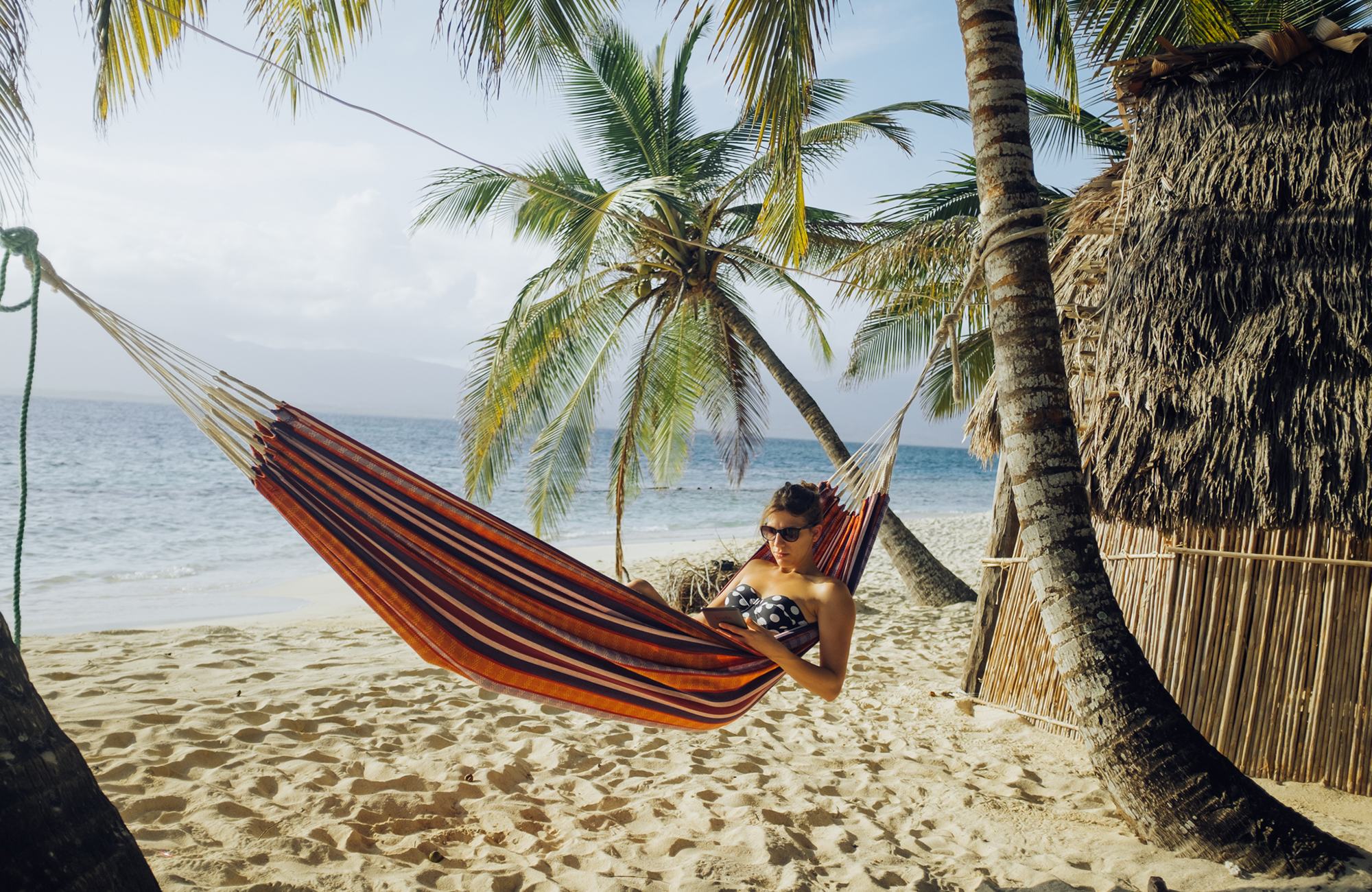 a student in a travelling classroom in a hammock on the beach